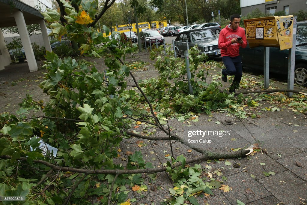 A man runs past torn tree limbs during a storm front on October 5, 2017 in Berlin, Germany. Storm front 'Xavier' is hitting northern and central Germany hard, leading to the closure of airports, rail lines, commuter trains and buses and even highways across the region. Authorities are reporting two deaths so far, both in Brandenburg state.