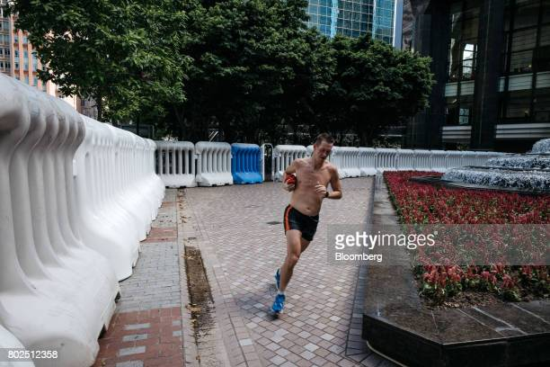 A man runs past water barricades near the Hong Kong Convention and Exhibition Center ahead of Chinese President Xi Jinping's arrival in Hong Kong...