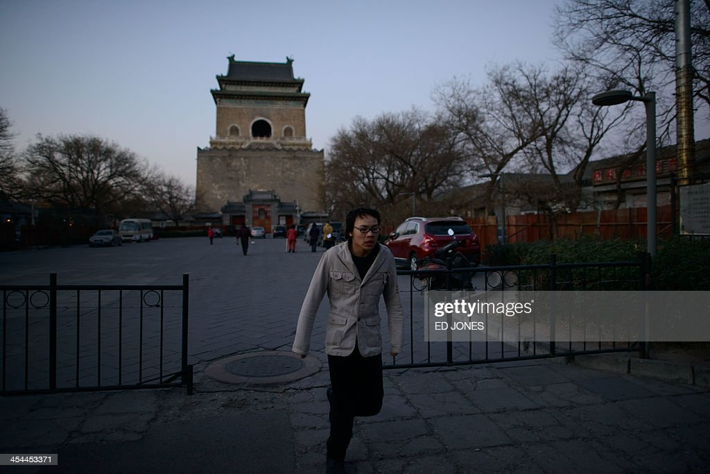A man runs through a gate before the Bell Tower -- once used for time keeping to inform the city's inhabitants of the arrival of morning, and dating back to the Han dynasty -- in Beijing on December 9, 2013. Chinese inflation decelerated to 3.0 percent in November, the National Bureau of Statistics (NBS) said, well under the government's target for the year. AFP PHOTO / Ed Jones