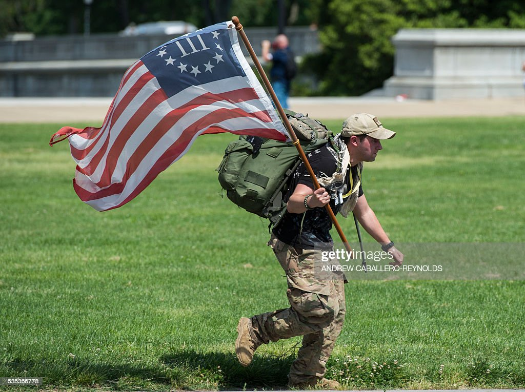A man runs with the American flag during the annual Rolling Thunder 'Ride for Freedom' parade ahead of Memorial Day in Washington, DC, on May 29, 2016. / AFP / Andrew Caballero-Reynolds