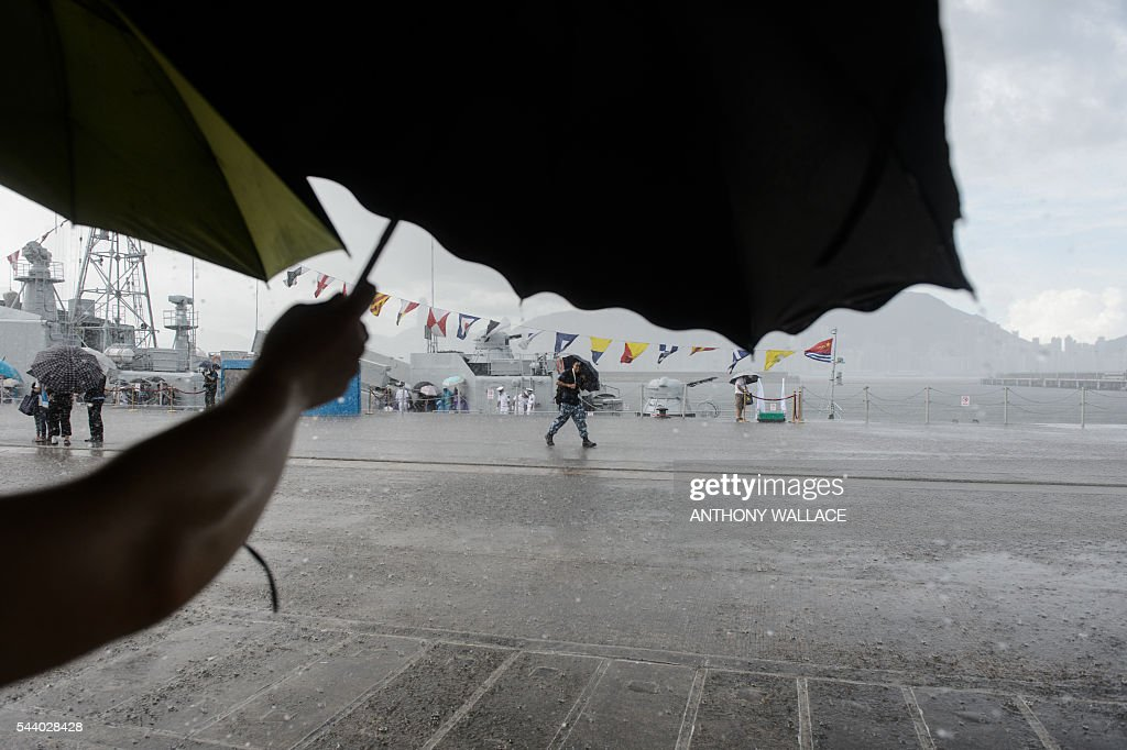 A man (C) rushes for cover as it rains heavily during the open day of the Chinese People's Liberation Army (PLA) Navy Base at Stonecutter Island in Hong Kong on July 1, 2016, to mark the 19th anniversary of the Hong Kong handover to China . / AFP / Anthony Wallace