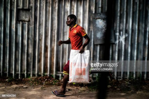 A man rushes through a street in Lagos on May 23 2017 / AFP PHOTO / MARCO LONGARI