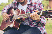 Man 's hand playing guitar, sitting on green grass. Nature background. Music, guitar and nature. Country folk song from acoustic guitar. Man holding his guitar.