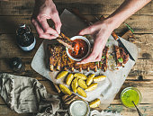 Man eating roasted pork ribs with potato pieces, garlic, rosemary and green herb sauce on rustic wooden table. Man's hands dipping piece of meat to ketchup in white bowl , top view