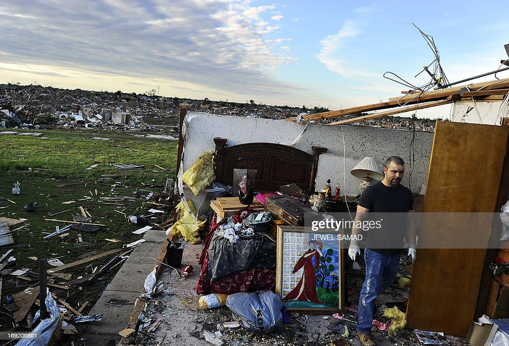 A man salvages stuff from what left of a bedroom of his tornado devastated home on May 21, 2013 in Moore, Oklahoma. Families returned to a blasted moonscape that had been an American suburb Tuesday after a monstrous tornado tore through the outskirts of Oklahoma City, killing at least 24 people. Nine children were among the dead and entire neighborhoods vanished, with often the foundations being the only thing left of what used to be houses and cars tossed like toys and heaped in big piles. AFP PHOTO/Jewel Samad