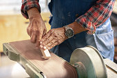 A man is using a machine to sand a piece of wood. The photo is a close-up of his hands and the machine.