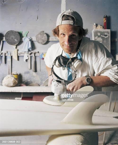 Man sanding surfboard in workshop, portrait