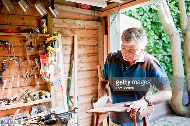 Man sanding wood in workshop