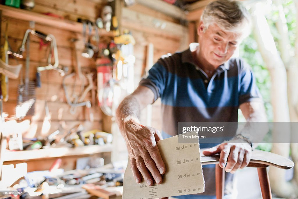 Man sanding wood in workshop : Stock Photo