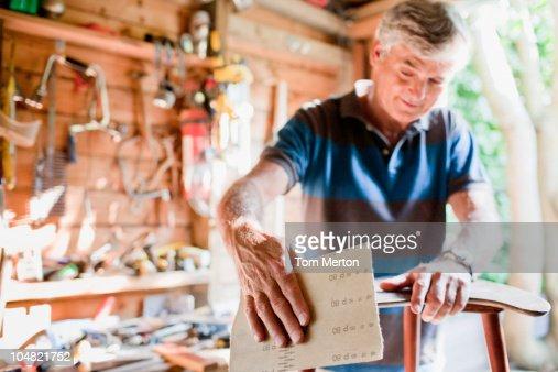 Man sanding wood in workshop