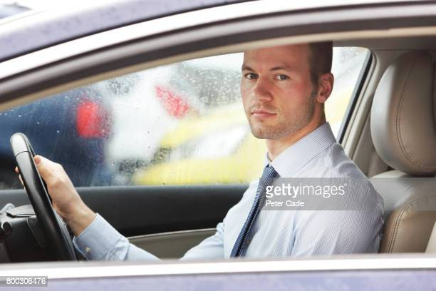 Man sat in car wearing shirt and tie