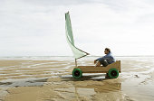 Man sat in home made go kart with sail, on beach