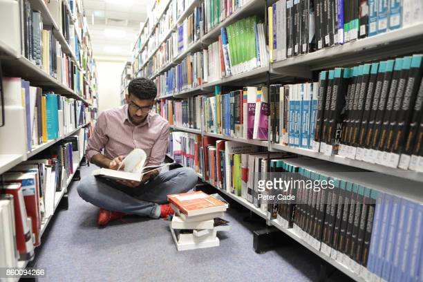 Man sat in library aisle reading book