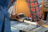 A man is using an electric sawing machine to saw a piece of wood. The photo is a close-up of his hands and the machine.