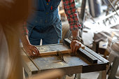 A man is using an electric sawing machine to saw a piece of wood.