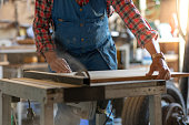 A man in a flannel shirt and a blue safety overall is sawing a plank in a workshop.