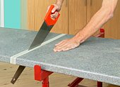 Man sawing through worktop using hand saw