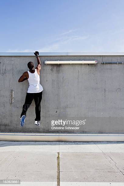 Man scaling wall on city street