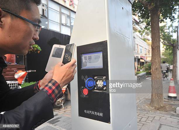 A man scan QR code on an intelligent lamp post on October 27 2015 in Shanghai China Intelligent lamp posts that contain lighting charging Wifi...