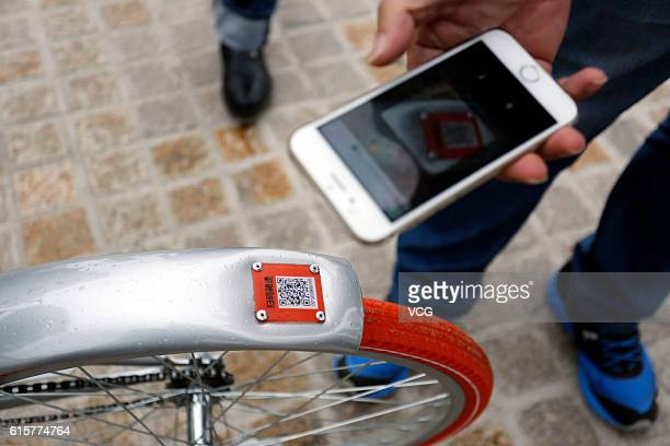 A man scans the QR code on the Mobike Lite at Baoshan District on October 19 2016 in Shanghai China The bikesharing service company Mobike released a...