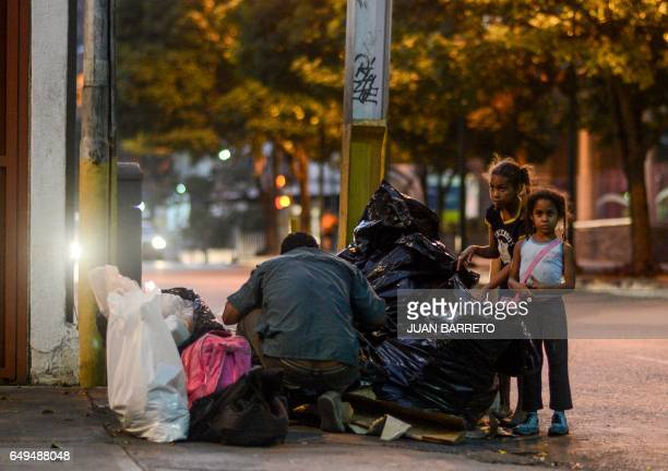 A man scavenges for food next to girls in the streets of Caracas on February 21 2017 Venezuelan President Nicolas Maduro is resisting opposition...