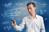 Man scientist or student working with various high school maths and science formulas standing on blue background.