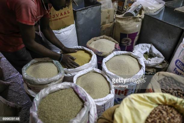 A man scoops up millet from a sack for a photograph at a wholesale market in Bengaluru India on Saturday June 10 2017 Millets were a staple in India...