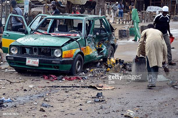 A man scouts for valuables beside a taxi damaged following an Improvised Explosive Devices at Gomboru market in Maiduguri Borno State in northeastern...