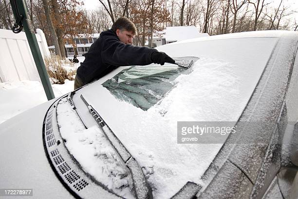 A man scraping ice and snow from the windshield