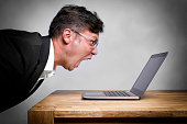Man sitting at the table and screaming at his laptop