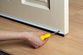 Man screwing brush seal to edge of door