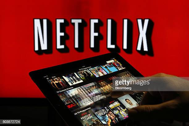 A man scrolls through a selection of viewing choices on the Netflix Inc application on a tablet device in this arranged photograph in London UK on...
