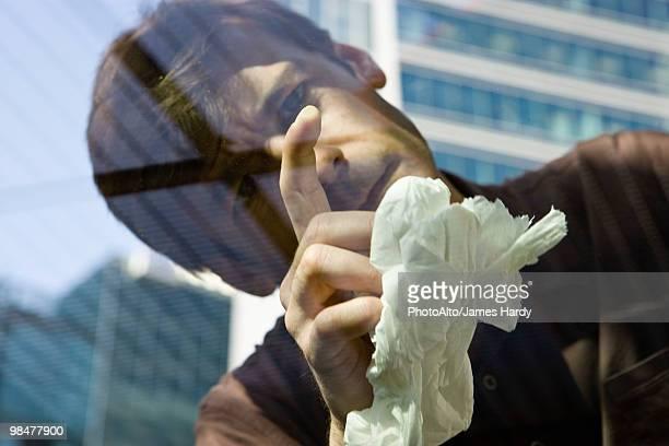 Man scrutinizing spot on car window glass