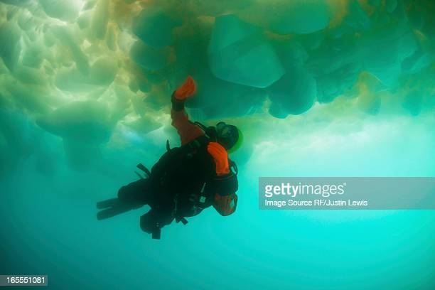 Man scuba diving under glacier