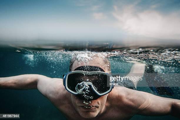 Mann Tauchen unter Wasser im See mit Maske