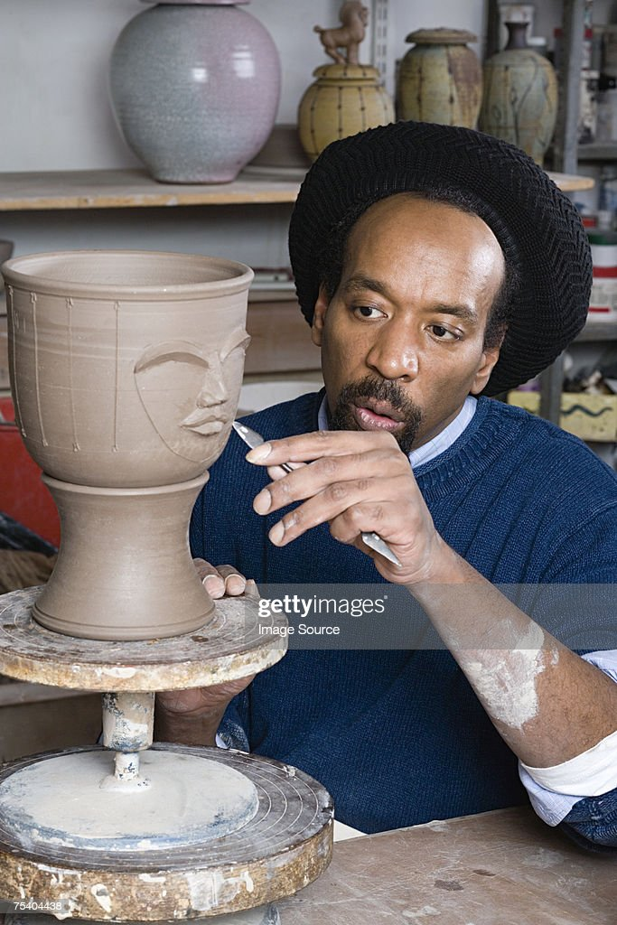 Man sculpting a face into vase : Stock Photo