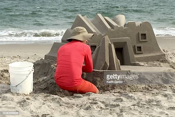 A man sculpting a sand castle at the ocean's edge Fort Tilden Beach Gateway National Recreation Area Rockaway Peninsula Queens NYC USA July 12 2015