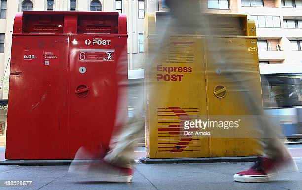 A man scuttles past a Post Office Box outside the Darlinghurst Post Office on May 7 2014 in Sydney Australia Australia Post is considering a userpay...