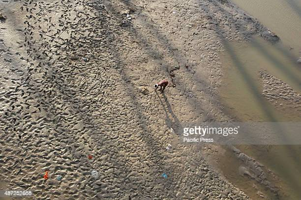 A man searches for coins in the muddy area of River Ganga that were offered by Hindu devotees during the water flood