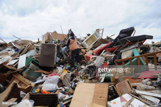 A man searches for objects between the tons of debris caused by the flood during Sunday's rainstorm on September 16 2017 in Livorno Italy Livorno in...