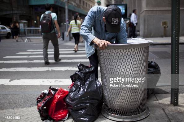 A man searches for recyclable bottles and cans near the New York Stock Exchange June 8 2012 on Wall Street in New York City