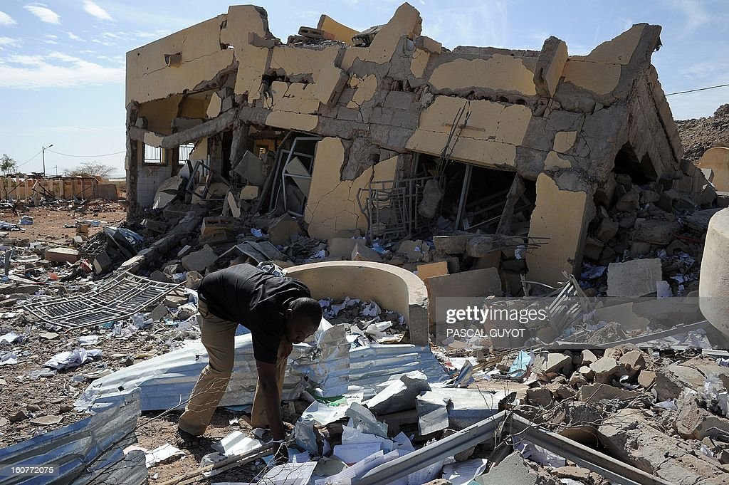 A man searches on February 5, 2013 in the ruins of a building destroyed by French air strikes in Douentza.The town was retaken by French and Malian troops in January. AFP PHOTO / PASCAL GUYOT