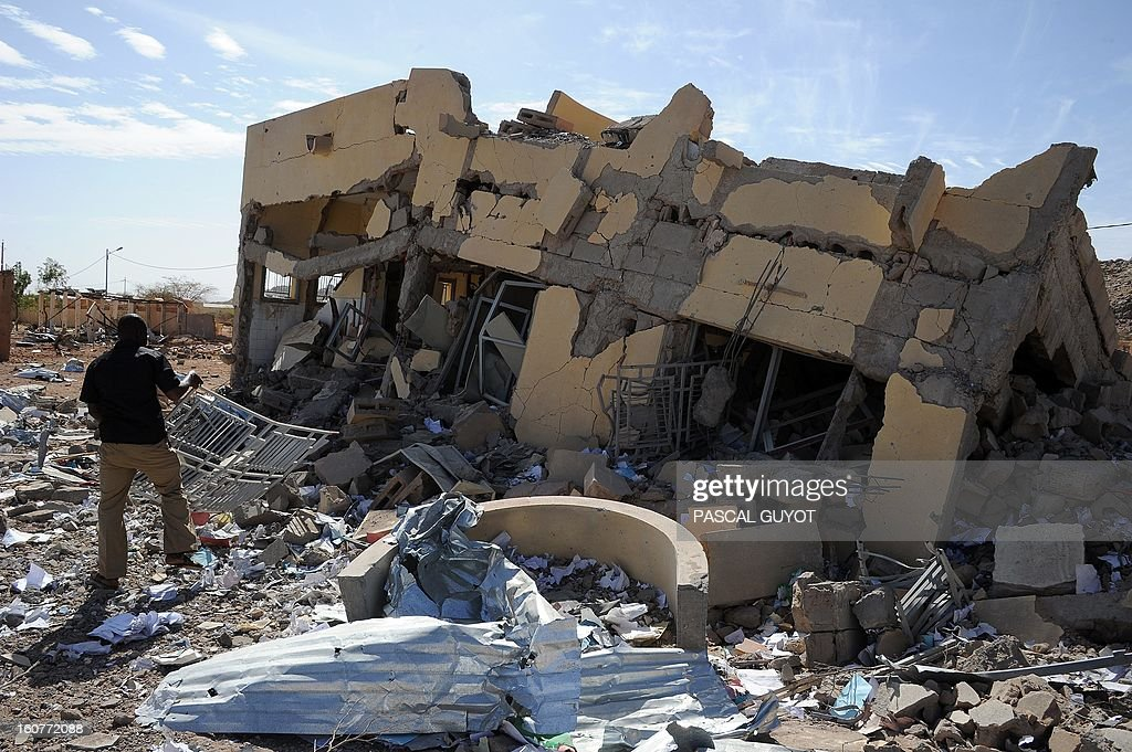 A man searches on February 5, 2013 in the ruins of a building destroyed by French air strikes in Douentza.The town was retaken by French and Malian troops in January.