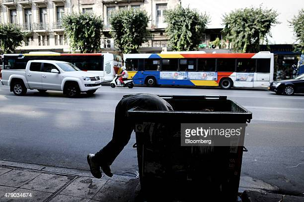 A man searches the contents of a public trash bin on a street in Thessaloniki Greece on Tuesday June 30 2015 Greece is staggering deeper into the...