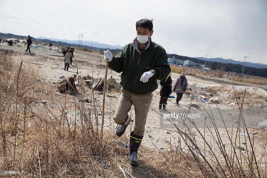 A man searches the missing at ukedo coast on March 11, 2014 in Fukushima, Japan. On March 11 Japan commemorates the third anniversary of the magnitude 9.0 earthquake and tsunami that claimed more than 18,000 lives, and subsequent nuclear disaster at the Fukushima Daiichi Nuclear Power Plant.