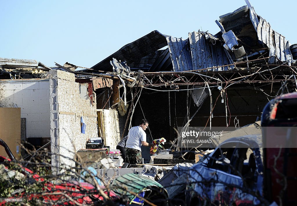 A man searches through debris at tornado devastated Plaza Towers Elementary School on May 22, 2013 in Moore, Oklahoma. Seven children died in the school during the tornado. As rescue efforts in Oklahoma wound down, residents turned to the daunting task of rebuilding a US heartland community shattered by a vast tornado that killed at least 24 people. The epic twister, two miles (three kilometers) across, flattened block after block of homes as it struck mid-afternoon on May 20, hurling cars through the air, downing power lines and setting off localized fires in a 45-minute rampage. AFP PHOTO/Jewel Samad