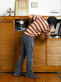Man searching cabinet for book in office