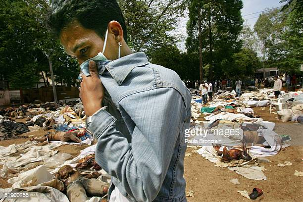 A man searching for his relatives is overcome by the smell of death at the Ban Muang temple which has become a makeshift morgue for hundreds of...
