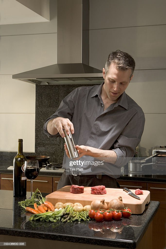 Man seasoning pieces of meat in kitchen : Stock Photo