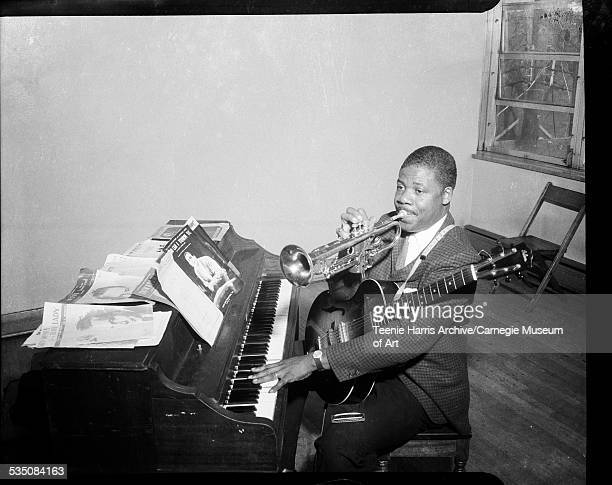 Man seated at piano holding guitar and playing trumpet with sheet music for 'Who Can I Turn To' by Leslie Bricusse and Anthony Newley Pittsburgh...